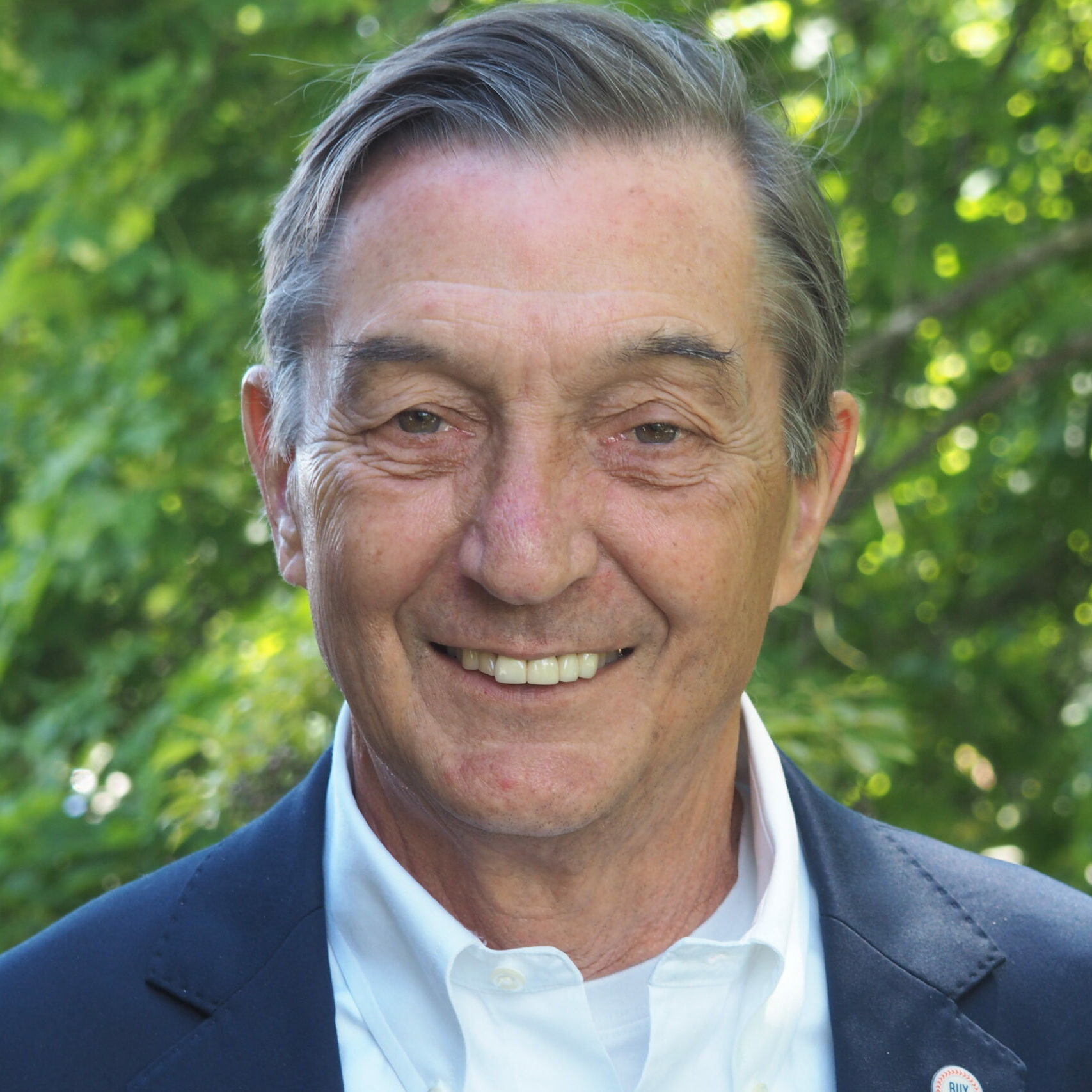 headshot of David Lepage wearing a suit while he smiles in front of greenery.