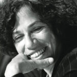 Black and white portrait of Nancy Neamtan. She has curly hair, and rests her chin on her hand as she smiles.